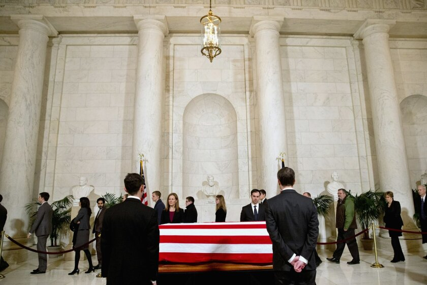 Supreme Court staff attend a private visitation in the Great Hall of the Supreme Court in Washington, Friday, Feb. 19, 2016, where late Supreme Court Justice Antonin Scalia lies in repose. (AP Photo/Jacquelyn Martin, Pool)