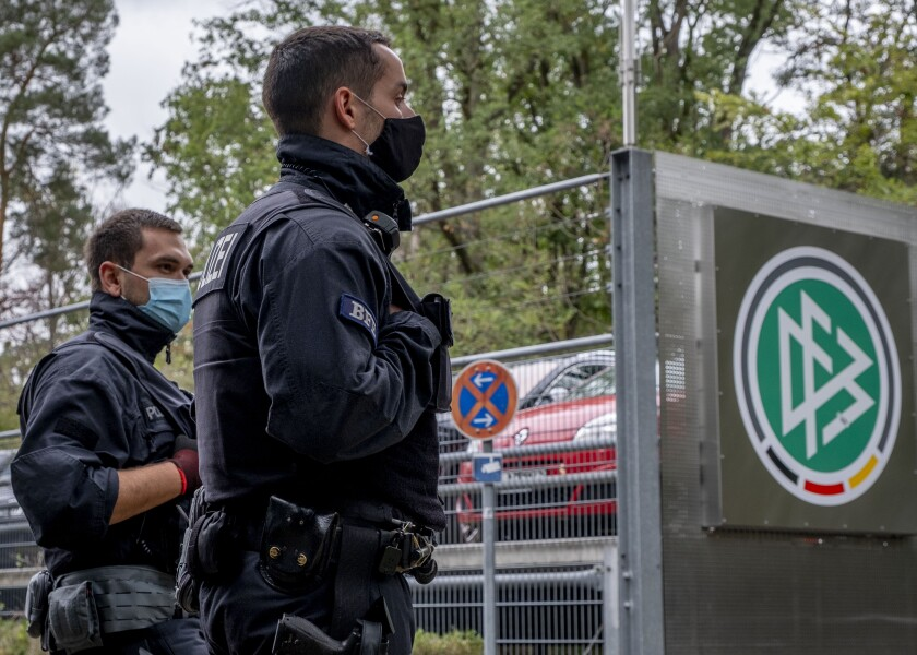 German police officers stand in front of the German football association DFB headquarters in Frankfurt, Germany, Wednesday, Oct.7, 2020. The public prosecutor's office in Frankfurt searched the offices of the DFB as well as the private homes of DFB officials on suspicion of tax evasion in particularly serious cases.2020. (AP Photo/Michael Probst)