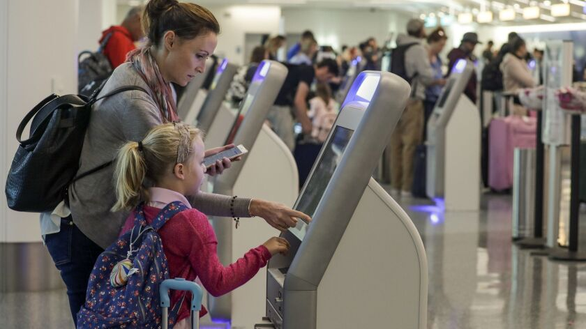 Katy Von Treskow, left, traveling with her 5-year-old daughter Madeline Von Treskow, uses self-check-in kiosk at Los Angeles International Airport on the day before Thanksgiving 2017.