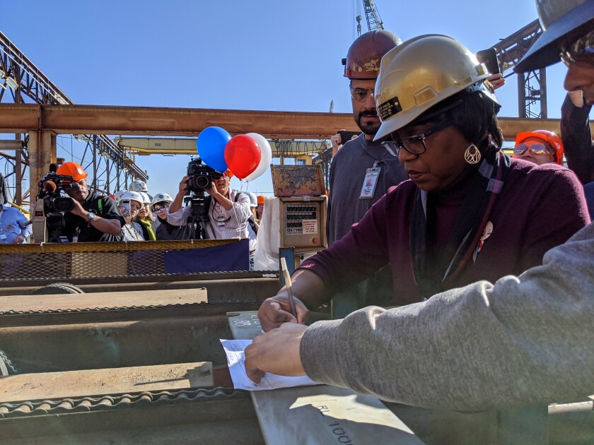 Kathy Baker, center, signs off on the ceremonial first cut of steel for the future Harvey Milk on Friday at General Dynamics NASSCO in San Diego.