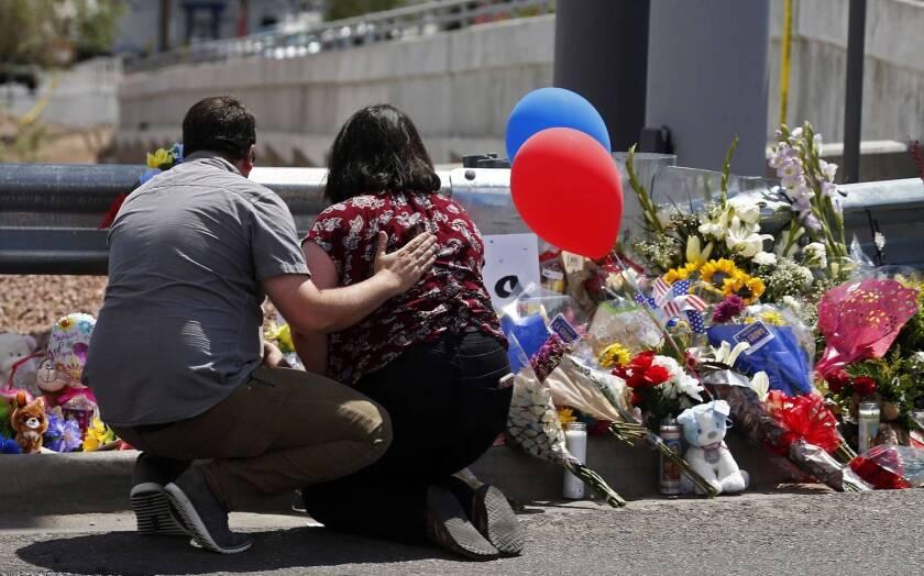 Dos personas dejan flores en recuerdo de las víctimas del tiroteo en El Paso, Texas.