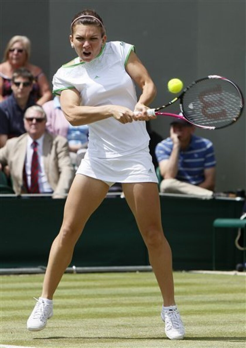 Romania's Simona Halep returns a shot to Serena Williams of the US during their match at the All England Lawn Tennis Championships at Wimbledon, Thursday, June 23, 2011. (AP Photo/Alastair Grant)