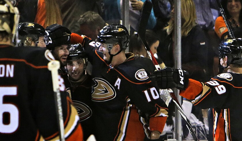 Ducks center Ryan Kesler gets a pat on the helmet from right wing Corey Perry (10) as they celebrate with left wing Matt Beleskey after their 3-2 overtime defeat of the Kings.