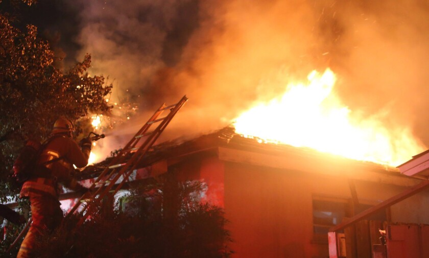 A firefighter battles a house fire in Granada Hills early Saturday morning. A 73-year-old woman died in the blaze.