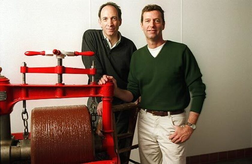 """Robert Steinberg, left, and John Scharffenberger of Scharffen Berger Chocolate Maker, in a 1998 photo, pose with a melangeur, a machine whose granite wheels blend chocolate and sugar. Steinberg """"changed chocolate from being seen as a mere sweet candy to having the status of a complex and interesting food. A new age of chocolate was started in this country with that company,"""" cookbook author Alice Medrich told The Times."""