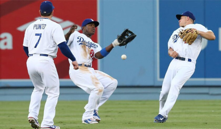 Dodgers center fielder Yasiel Puig drops a pop fly for an error between shortstop Nick Punto and second baseman Mark Ellis in the second inning against San Francisco on Saturday.