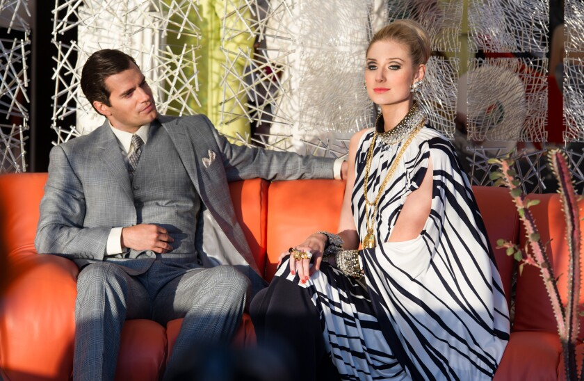 """Henry Cavill, in a Timothy Everest suit, and Elizabeth Debicki, in a black-and-white outfit partially inspired by Cruella de Vil, star in """"The Man From U.N.C.L.E."""""""