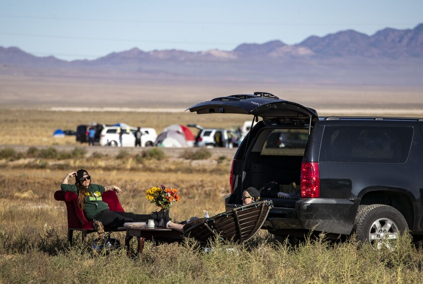 Two people sitting on chairs next to an SUV in the desert