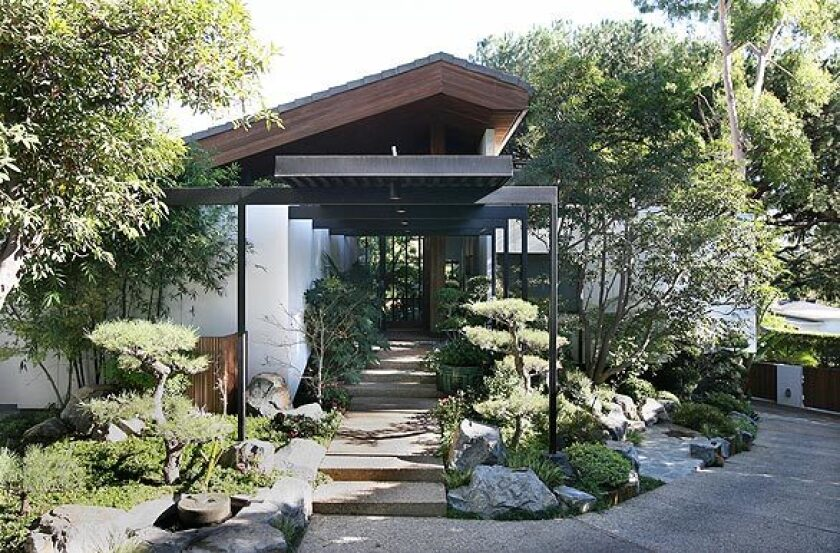 """Three years ago, Shulamit Nazarian bought a 1973 Holmby Hills home designed by architect A. Quincy Jones, former dean of USC's School of Architecture and widely regarded as one of Southern California's midcentury greats. Her goal: to preserve the architecture but make it her own, not some by-the-numbers retro palace. """"I didn't want to make the house a museum to midcentury,"""" Nazarian says. The front of the home is defined by its asymmetrical roof line and Japanese-inspired garden."""