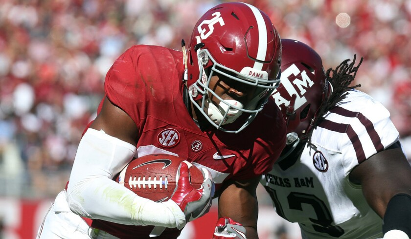 Alabama running back Joshua Jacobs, left, is knocked out of bounds by Texas A&M defensive lineman Reggie Chevis during the first half on Oct. 22.