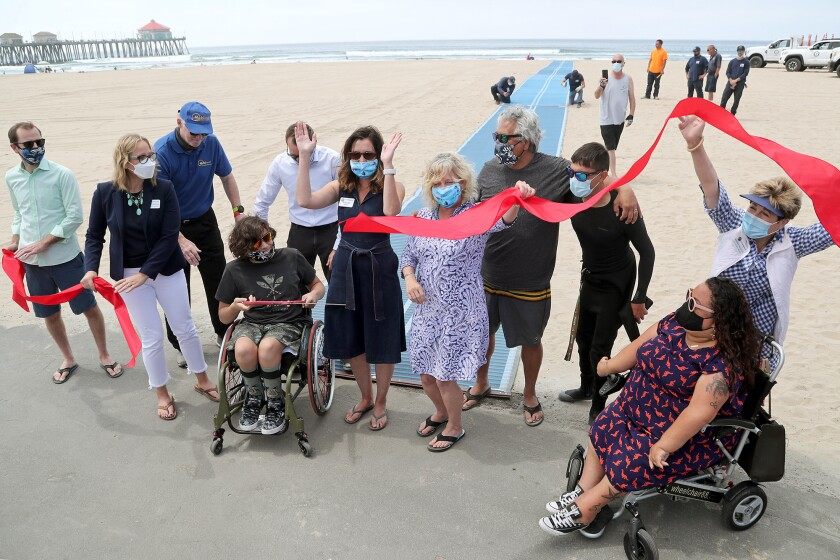 Members of the Huntington Beach City Council celebrate the first Mobi-Mat during a ribbon-cutting ceremony on Wednesday.