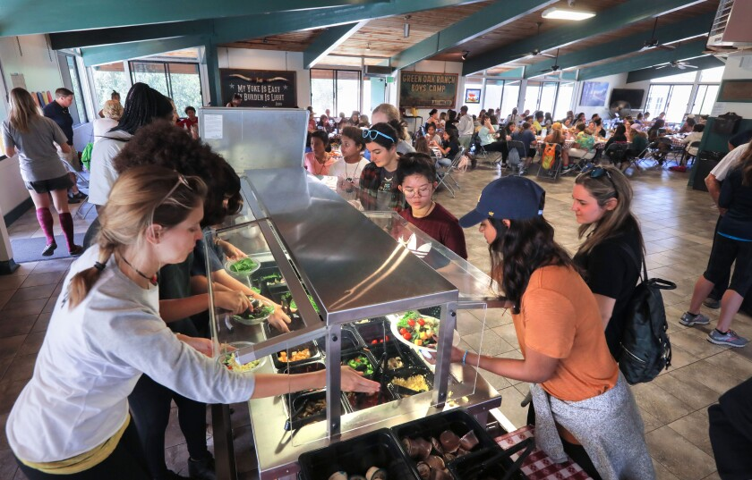 Experience Camp participants and staff members hit the salad bar (to go with the pizza) during lunch in the dining hall at Green Oak Ranch.