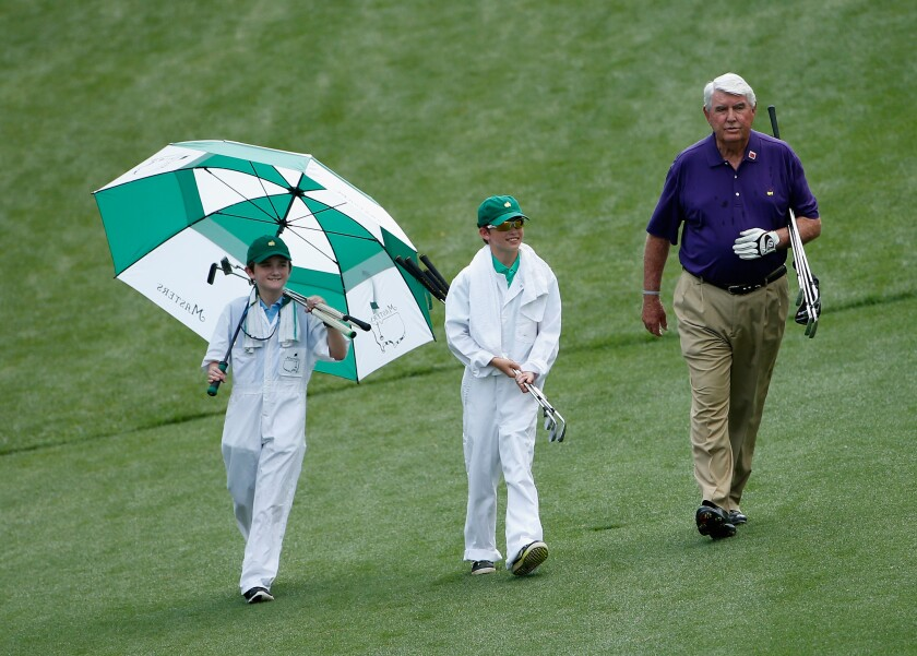 Charles Coody, who won the Masters in 1971, walks with two young caddies during the 2015 Par 3 Contest at August National Golf Club.