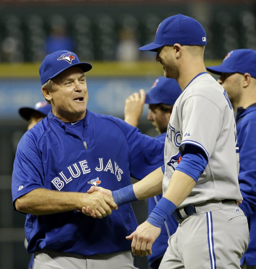 Toronto Blue Jays manager John Gibbons, left, shakes hands with Nolan Reimold after beating the Houston Astros 6-5 in a baseball game Thursday, July 31, 2014, in Houston. Reimold hit the game-winning home run. (AP Photo/David J. Phillip)
