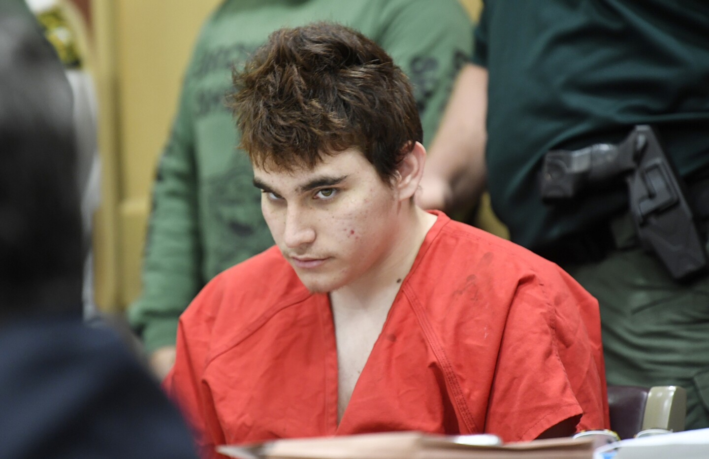 Florida school shooting suspect Nikolas Cruz quickly glances up at the prosecutors while in court back in court in front of Circuit Judge Elizabeth Scherer for a hearing to move forward the death penalty case Friday afternoon, April 27, 2018, in Fort Lauderdale, Fl. No trial date was set and Cruz was granted a waiver on Florida's speedy trial rule. The rule generally requires that a felony defendant go to trial within 175 days of arrest unless it's waived. Cruz, 19, is charged with 17 counts of murder and 17 counts of attempted murder in the February 14, 2018 school shooting at Marjory Stoneman Douglas High School in Parkland, Fl. Cruz's attorney has said he would plead guilty if guaranteed life without parole, but prosecutors are seeking the death penalty.