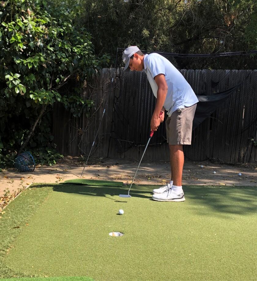 Ivan Barahona Jr. practices his putting at home.