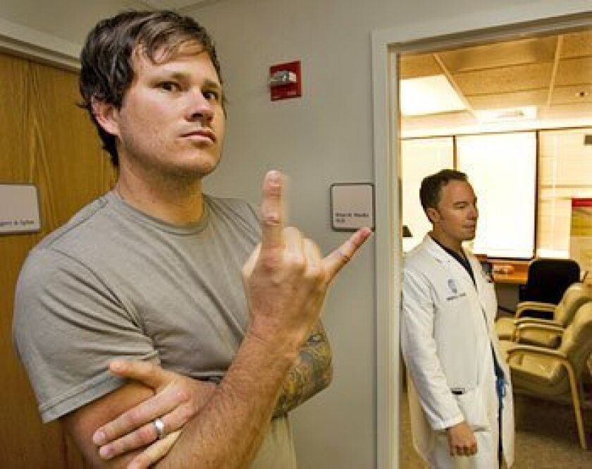Blink-182 singer and guitarist Tom DeLonge (left) of Rancho Santa Fe visited longtime friend and doctor Brian Weeks at Weeks' Alvarado Hospital office. (Howard Lipin / Union-Tribune)