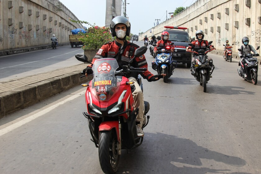 Motorcyclists in red-and-black jackets lead an ambulance.