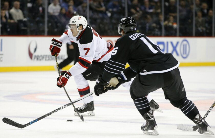 New Jersey Devils defenseman Jon Merrill (7) looks for a shot as New York Islanders right wing Cal Clutterbuck (15) defends during the first period of an NHL hockey game in New York, Tuesday, Nov. 3, 2015. (AP Photo/Kathy Willens)