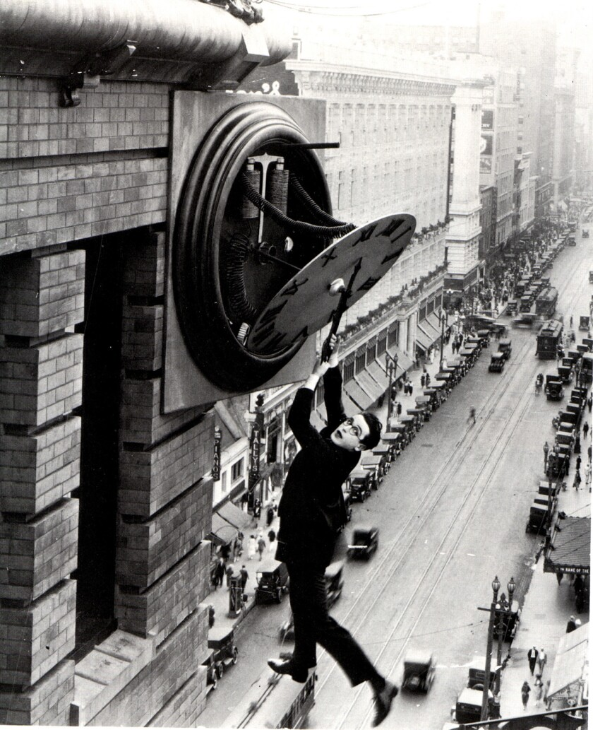 A man dangles from a clock face on the side of a building high above downtown L.A.