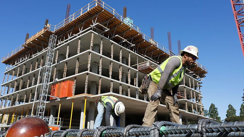 Local 229 ironworkers work Friday on La Jolla Village Drive.