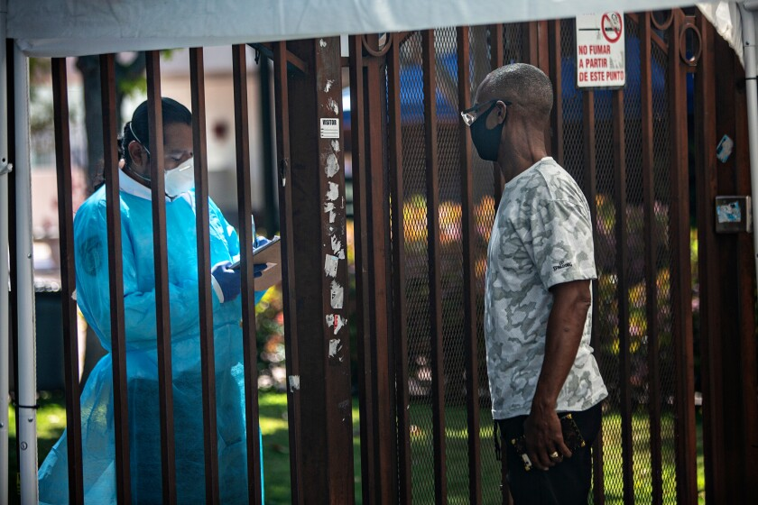 A man talks with a healthcare worker outside Kedren Community Health Center during the coronavirus pandemic in Los Angeles
