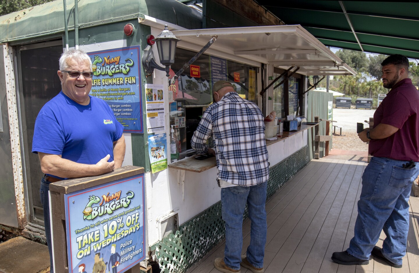 Charlie Webster, left, stands outside the Nessy Burgers, the Fallbrook hamburger stand that his late wife, Sandra, co-founded in 1989.