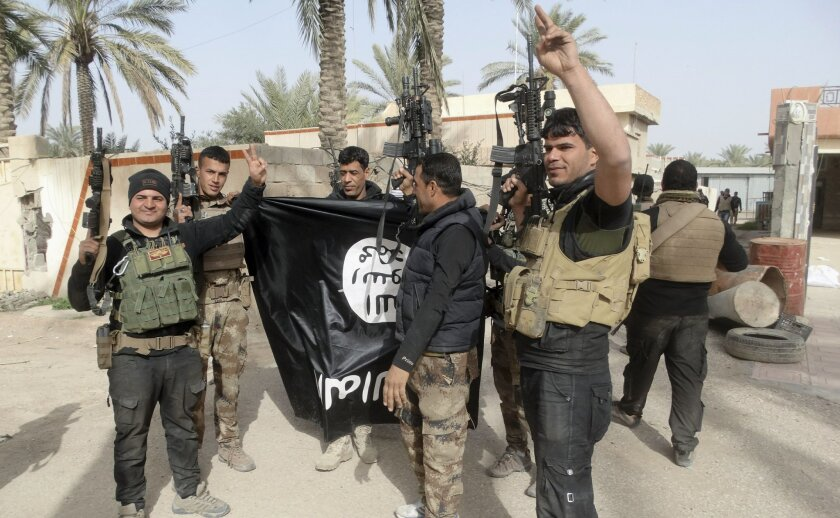 FILE -- In this Tuesday, Jan. 19, 2016 file  photo, Iraqi security forces celebrate as they hold a flag of the Islamic State group they captured in Ramadi, 70 miles (115 kilometers) west of Baghdad, Iraq. Iraqi security forces and the U.S.-led coalition say the government has regained full control