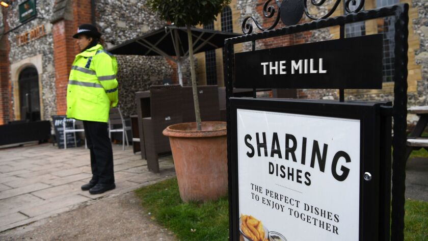A police officer stands near the cordoned-off Mill pub in Salisbury, England, on Sunday.