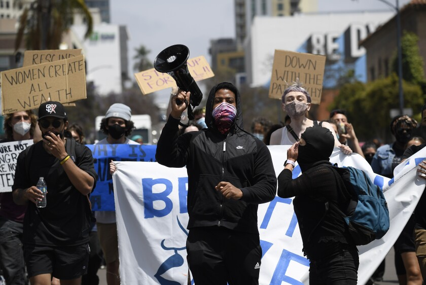 Protesters chant as they march through downtown San Diego