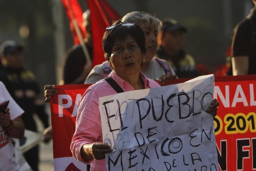 """Un grupo de personas participan en una manifestación hoy, martes 2 de enero de 2018, en Ciudad de México (México), contra la Ley de Seguridad Interior, que formaliza el papel de las Fuerzas Armadas en tareas de seguridad pública, bajo el argumento de que """"fortalece el autoritarismo"""" en el país. EFE"""