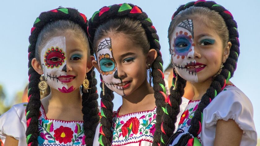 Kids get their faces painted at the Night of Altars, which is held every year by El Centro Cultural