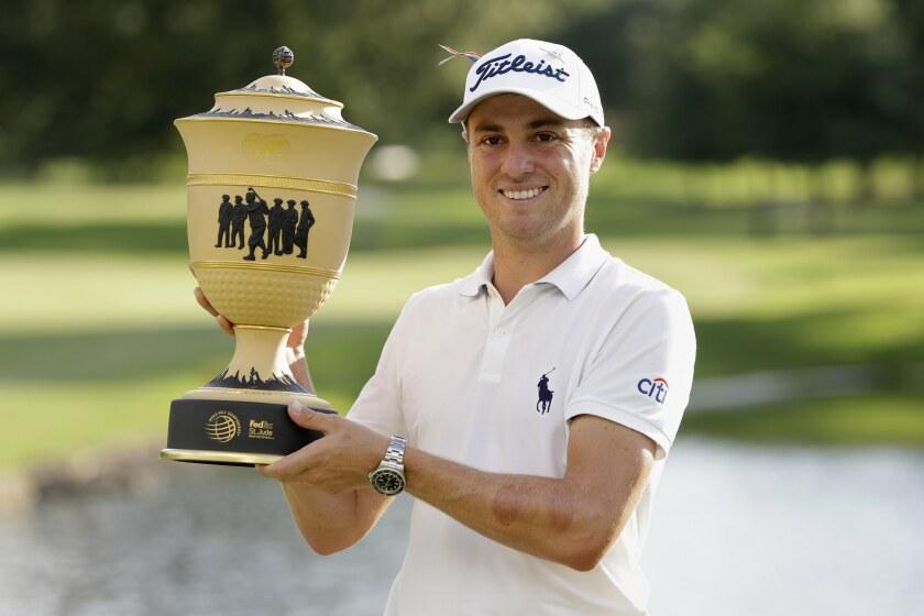 Justin Thomas sostiene el trofeo después de ganar el FedEx Invitational del Campeonato Mundial de Golf
