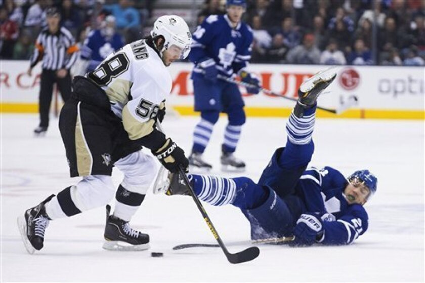 Toronto Maple Leafs' James van Riemsdyk, right, plays a pass beyond Pittsburgh Penguins Kris Letang during second period NHL hockey action in Toronto on Saturday, March 9, 2013. (AP Photo/The Canadian Press, Chris Young)