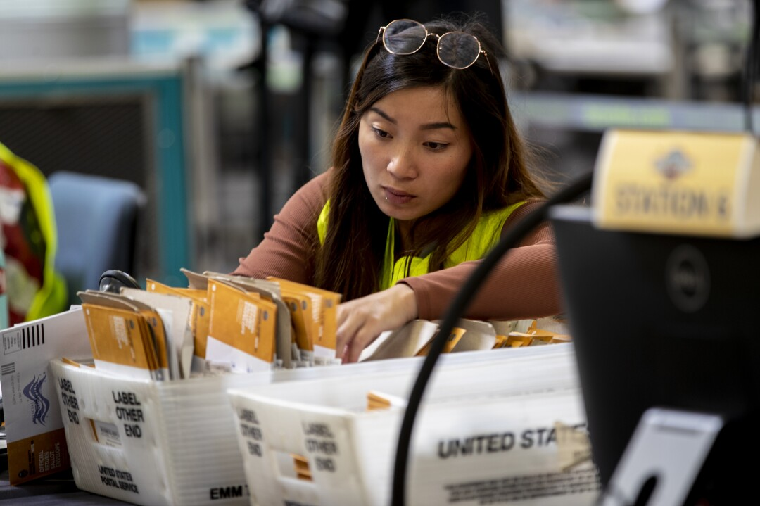 Ein Wahlhelfer überprüft die Unterschriften auf den Stimmzetteln am Tag der Rückrufwahl