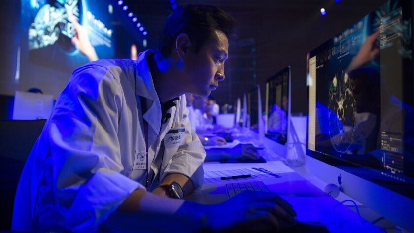"""A doctor examines a magnetic resonance image of a human brain during the competition against an artificial intelligence """"physician"""" at the China National Convention Center in Beijing on June 30, 2018."""