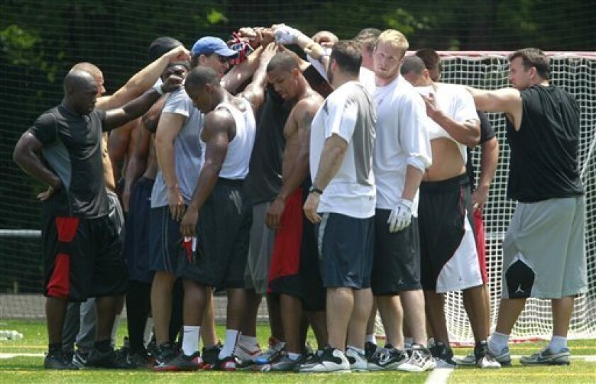 Members of the New York Giants huddle during an unofficial football workout at Bergen Catholic High School, Friday, June 10, 2011 in Oradell, N.J. The workout gives the players an opportunity to practice together during the NFL labor lockout. (AP Photo/Julio Cortez)