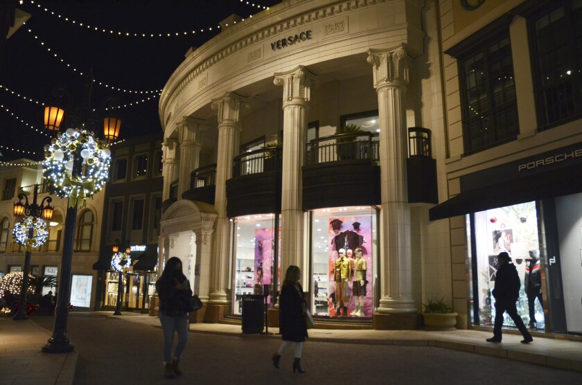 "People walk near the Versace boutique on Rodeo Drive, decorated for the holidays amid the coronavirus pandemic, Monday, Nov. 30, 2020, in Beverly Hills, Calif. The three-week ""safer at home"" order began on Monday. Indoor retail businesses, which make much of their profits during the Thanksgiving and Christmas holiday seasons, are allowed to remain open but with just 20% of capacity, including nail salons and other personal care services. (AP Photo/Pamela Hassell)"