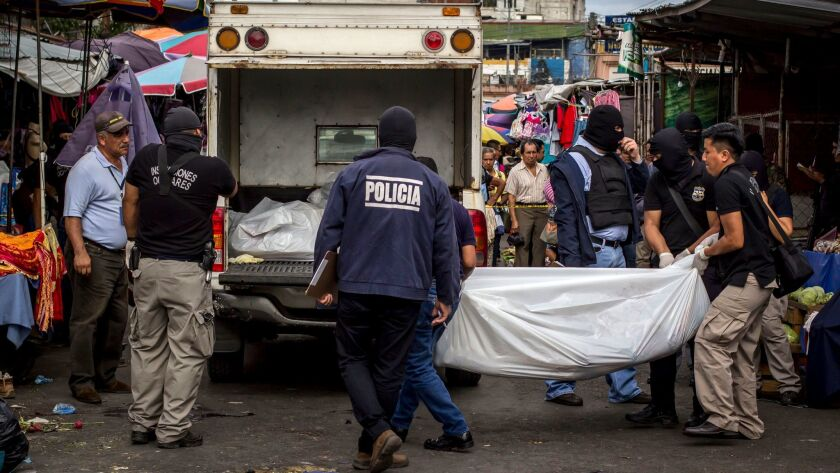 Police investigators carry a body to a forensic vehicle, after a shootout between private security guards and gang members, at the central market in San Salvador, El Salvador on March 15, 2017.