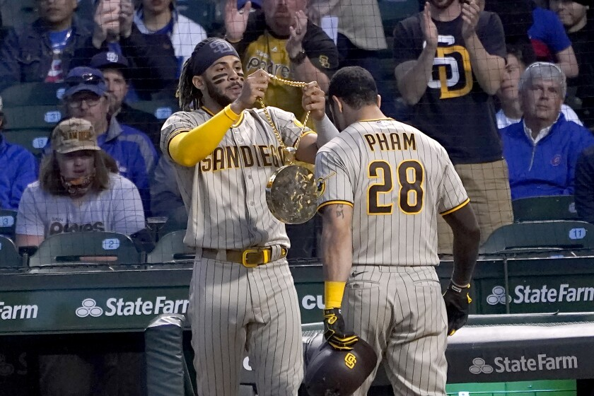 San Diego Padres' Tommy Pham (28) gets the chain swag from Fernando Tatis Jr. after Pham hit a two-run hime run off Chicago Cubs starting pitcher Kyle Hendricks during the fifth inning of a baseball game Tuesday, June 1, 2021, in Chicago. (AP Photo/Charles Rex Arbogast)
