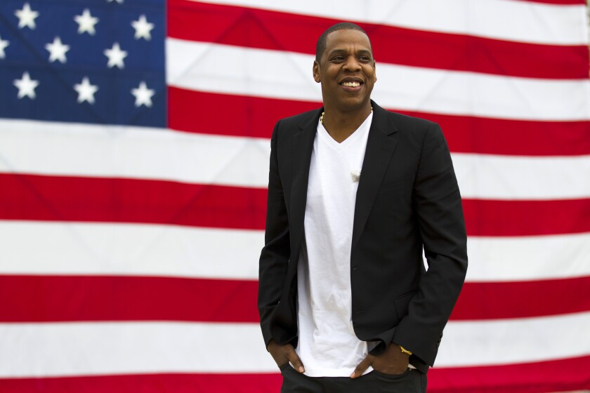 """FILE - In this May 14, 2012 file photo, entertainer Shawn """"Jay-Z"""" Carter smiles in between interviews, after a news conference at Philadelphia Museum of Art in Philadelphia. Jay-Z's annual festival in Philadelphia, Made in America, won't take place Labor Day weekend due to the coronavirus pandemic. In a statement Wednesday, July 1, 2020, the rap mogul's Roc Nation company said they plan to produce the popular festival in 2021. (AP Photo/Matt Rourke, file)"""