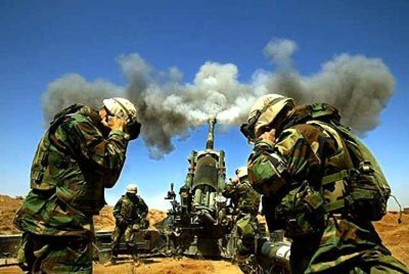U.S. Marines shield their ears from the roar of a 155-millimeter howitzer firing on Iraqi positions south of Baghdad.