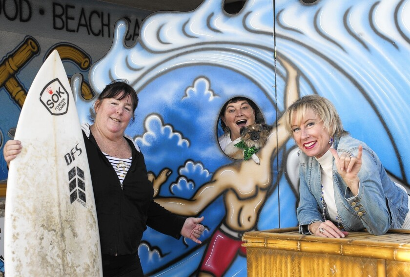 From left, Claudia Patrice, Lee Love and Kathleen Johnson, all of Surf City Splash, pose for a portrait at Zack's in Huntington Beach. The annual Surf City Splash, where people go into the Pacific Ocean on New Year's Day, is a fundraiser for the International Surfing Museum.