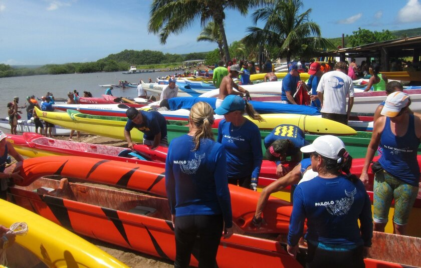 At the finish line on Molokai, the beach is awash in colorful outrigger canoes and paddlers in team jerseys for the ninth annual Pailolo Challenge.