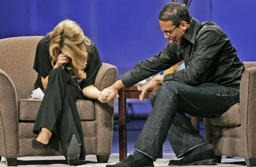 Carrie Prejean prayed with pastor Miles McPherson (right) as they shared the stage during services yesterday The Rock Church in Point Loma. (Nancee E. Lewis / Union-Tribune)