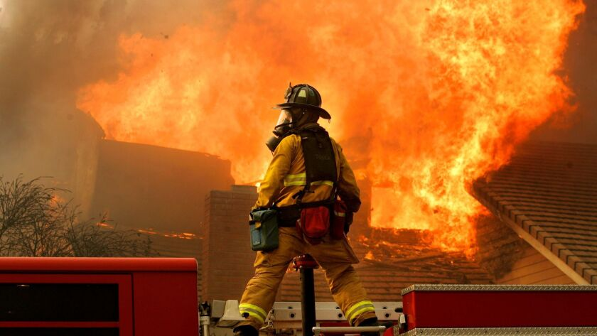 A San Diego firefighter confronts a blaze in Rancho Bernardo during a firestorm on Monday, October 22, 2007.