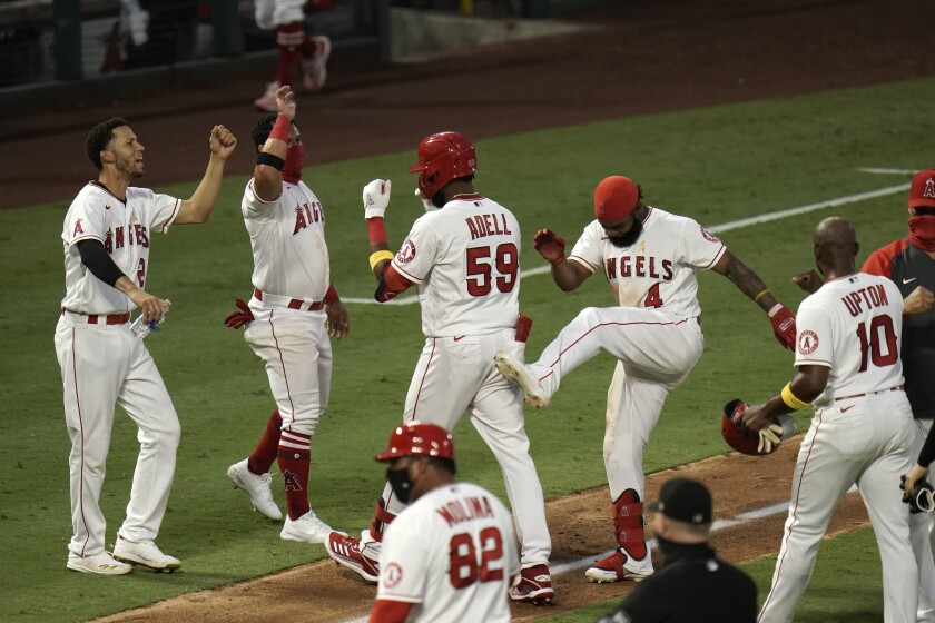 The Angels' Jo Adell and teammates celebrate his seventh-inning, walk-off single against the Astros.