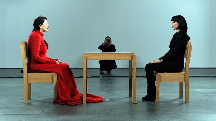 "Artist Marina Abramovic, left, performs during ""Marina Abramovic: The Artist Is Present"" exhibition at the Museum of Modern Art in 2010."