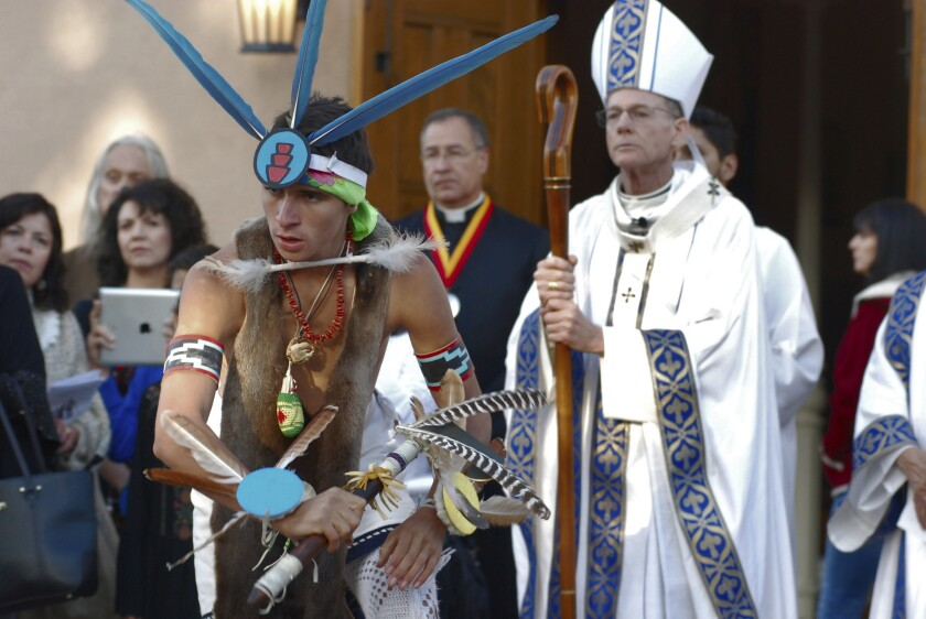 Dezmund Marcus of Ohkay Owingeh, N.M., performs the butterfly dance at the outset of an annual autumn festival in front of a crowd, including Roman Catholic Archbishop John Wester, right, on Friday, in Santa Fe, N.M.