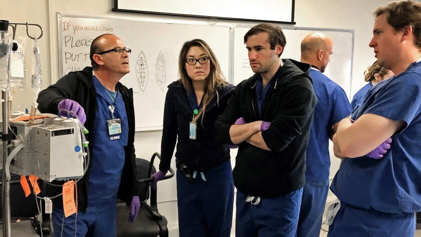 Nurse instructs surgical residents